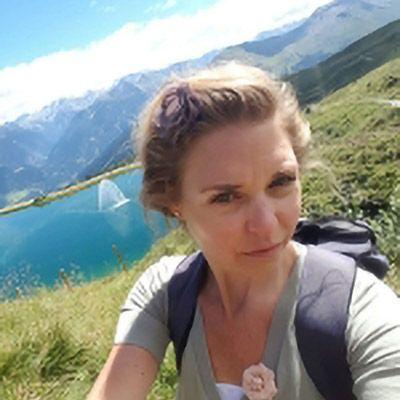 Frau mit See und Bergen im Hintergrund